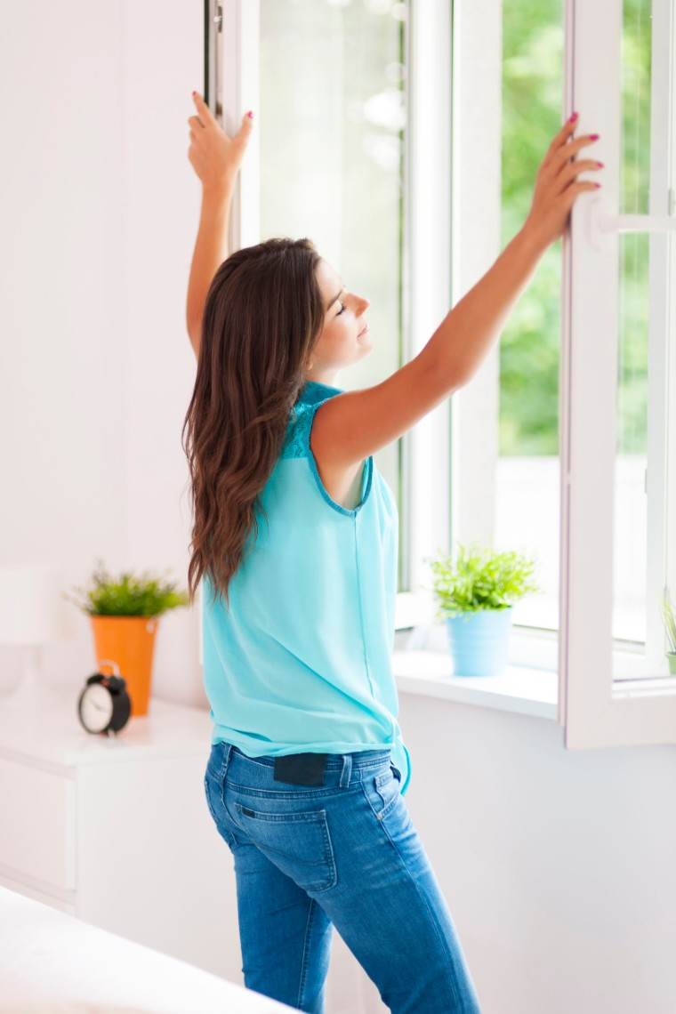 Woman opening window and breathing in fresh air.